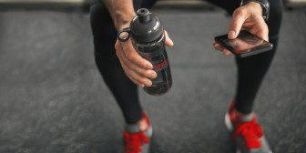 Someone in gym sitting with water bottle checking a phone - The Dark Side of Social Media Fitness Culture